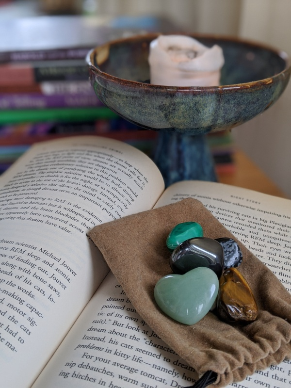 5 smooth stones on a book with a chalice in the background.